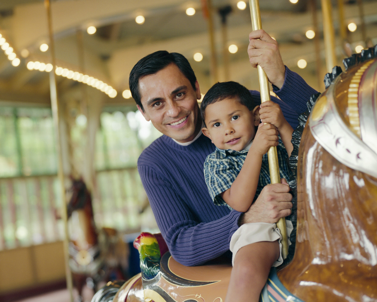 Father and Son Riding Carousel Horse