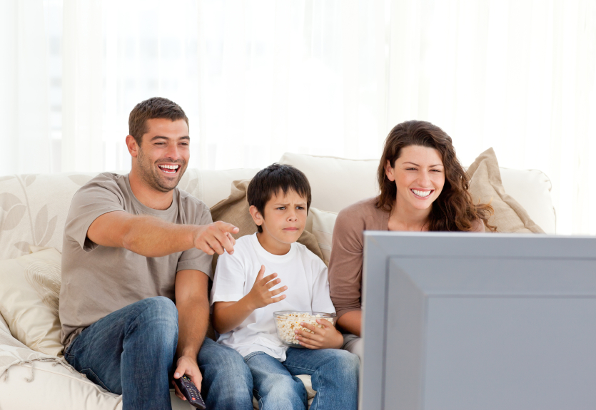 Family laughing while watching television together in the living-room