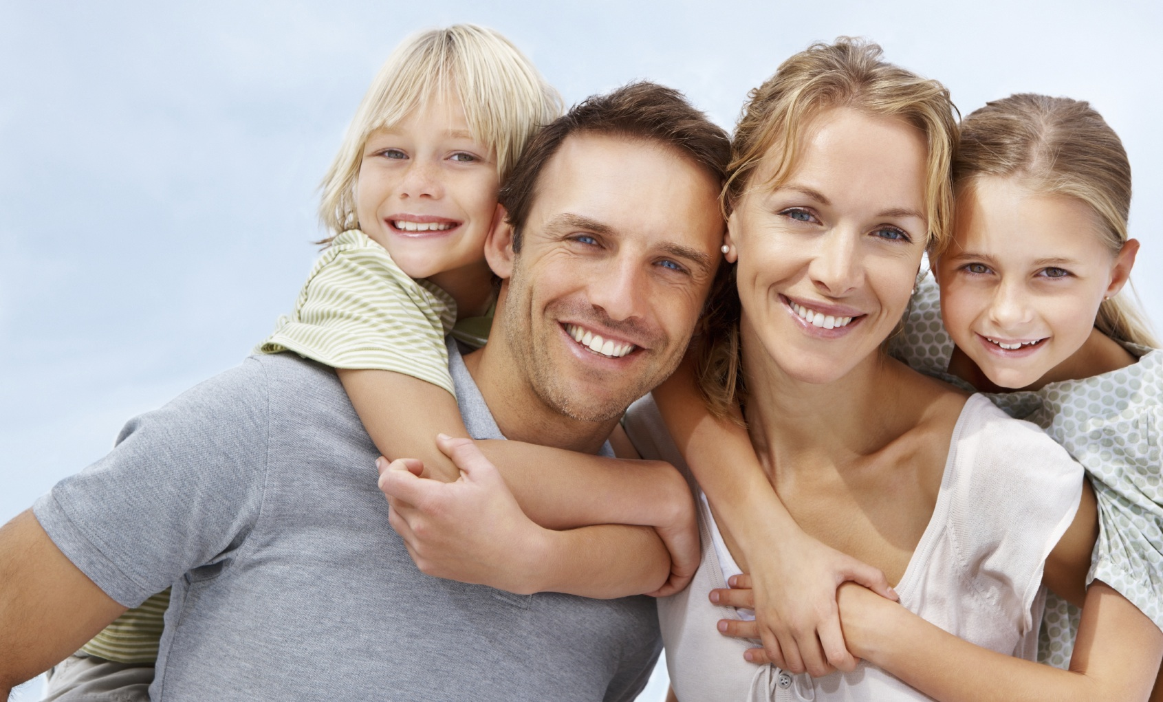 Portrait of a happy mature man and woman carrying kids on back