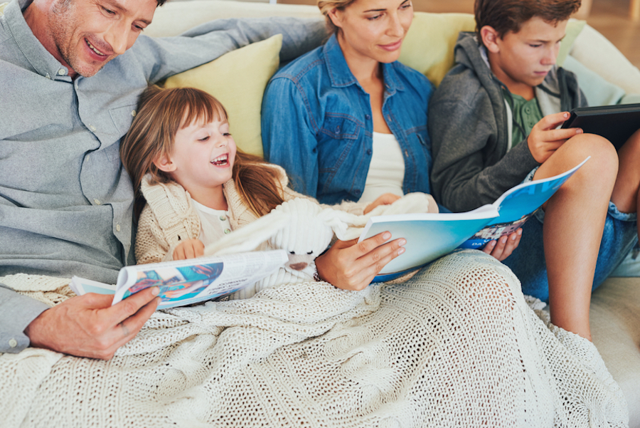 happy family reading newspaper, magazine and digital tablet on a cosy aftenoon